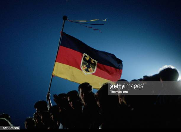 People waving a German Flag on German Unity Day on October 03 in Berlin Germany The year 1990 marks the 25th anniversary of the fall of the Berlin...