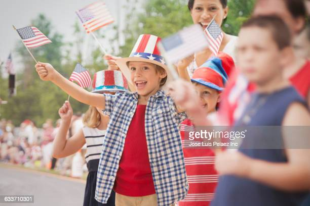 People waving flags at 4th of July parade
