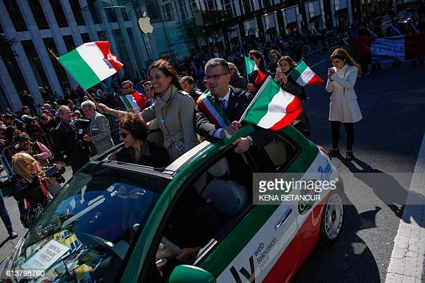 people waving Italian flags ride in a small car as they participate in the annual Columbus Day parade in New York on October 10 2016 / AFP / KENA...