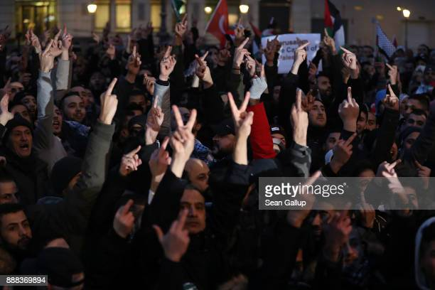 People waving Palestinian and Turkish flags hold up their middle finger in the direction of the US Embassy at the Brandenburg Gate to protest against...