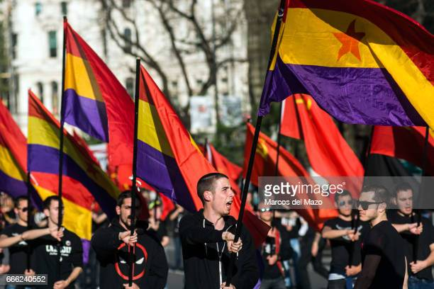 People waving republican and communist flags during a demonstration demanding a Spanish Republic