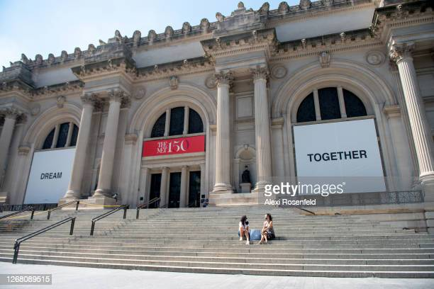 People weairng masks sit on the stairs at The Metropolitan Museum of Art where Yoko Ono's new art installation, Dream Together, is displayed on the...