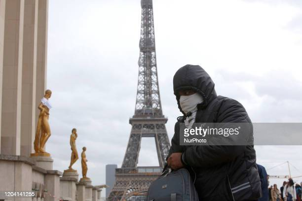 People wear a face mask on the Trocadero esplanade in front of the Eiffel Tower in Paris, France, February 29 as France confirmed a 73 persons...