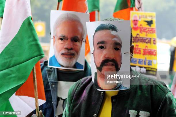 People wear a mask in the likeness of Indian Air Force pilot Abhinandan Varthaman right and Indian Prime Minister Narendra Modi during a rally in New...