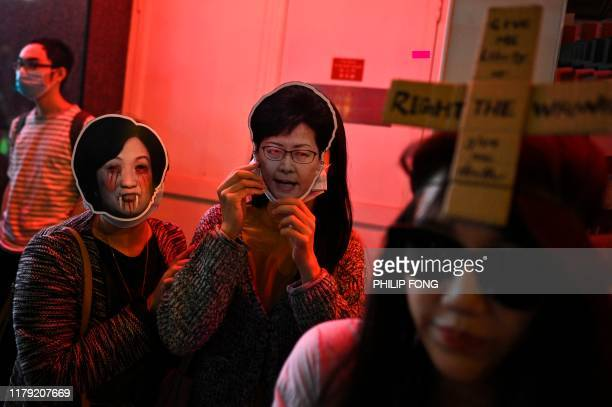People wear a mask of pro-Beijing establishment lawmaker Regina Ip and Hong Kong's chief executive Carrie Lam join a march to Central district during...