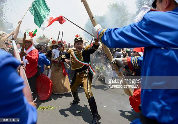 People wear costume along the streets of the Penon de los Banos neighborhood in Mexico City on May 5 commemorating the anniversary of Mexico's...