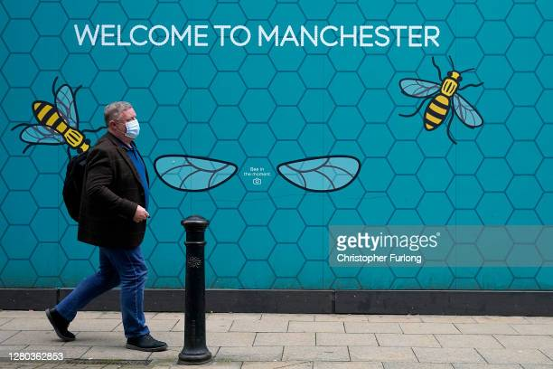 People wear Covid-19 protection face masks as they walk through the city centre on October 15, 2020 in Manchester, England. Manchester was placed in...