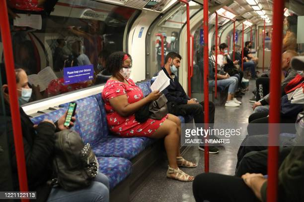 People wear face coverings as a precaution against COVID-19 on a London Underground tube train in London on June 20, 2020 during the coronavirus...