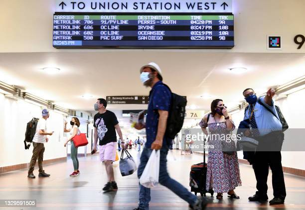People wear face coverings as they pass through Union Station on July 19, 2021 in Los Angeles, California. A new mask mandate went into effect just...