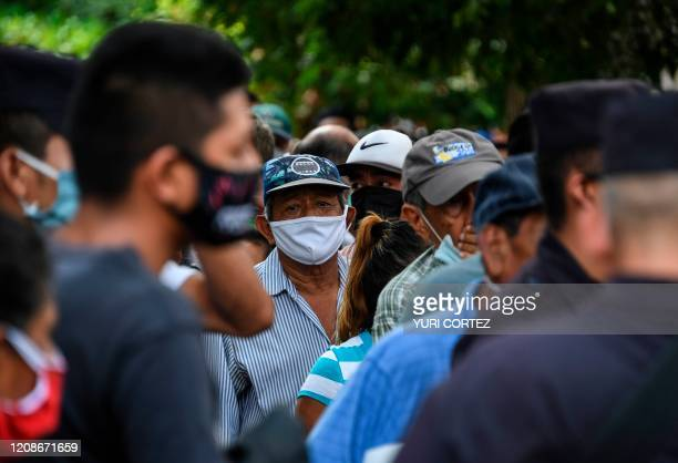 People wear face masks against the spread of the new coronavirus as they queue to enter a bank in San Salvador on March 30 2020 Thousands of...
