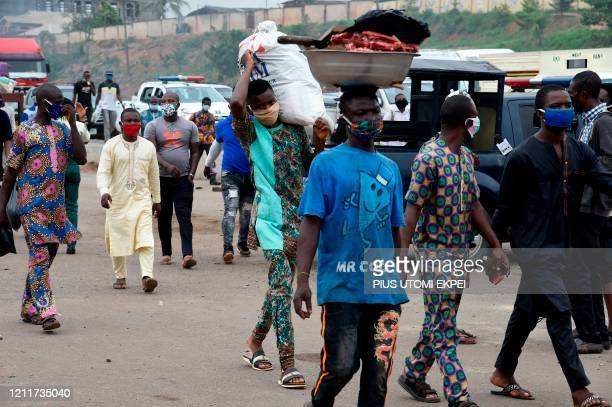 People wear face masks ahead police checkpoint in compliance with state directive to curb the spread of COVID-19 coronavirus at Ojodu-Berger in...