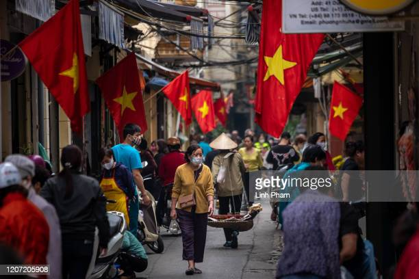 People wear face masks amid concerns of the spread of the COVID-19 Coronavirus while shopping at a local market on March 15, 2020 in Hanoi, Vietnam....