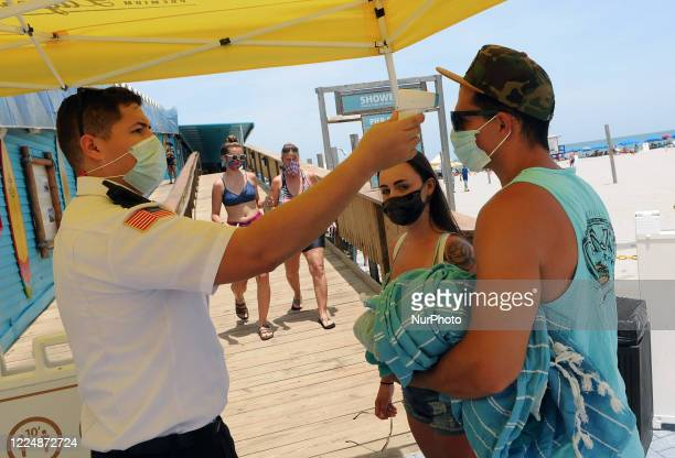 People wear face masks and undergo mandatory temperature checks before entering the pier on Independence Day July 4 in Cocoa Beach Florida Crowds at...