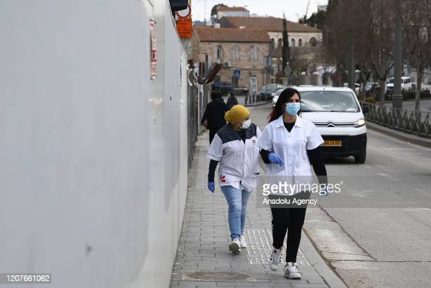 People wear face masks as a precaution against the coronavirus at a tram station in Shuafat district in Jerusalem on March 19, 2020.