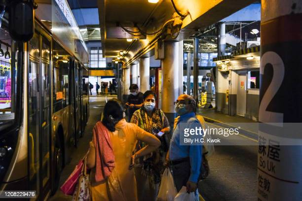 People wear face masks as a precaution against the spread of Coronavirus waiting at a bus stop during a coronavirus outbreak on March 26 2020 in Hong...