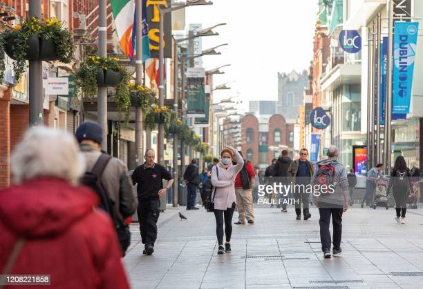 People wear face masks as a precautionary measure against covid-19, as they walk past shops in Dublin, on March 25 after Ireland introduced measures...