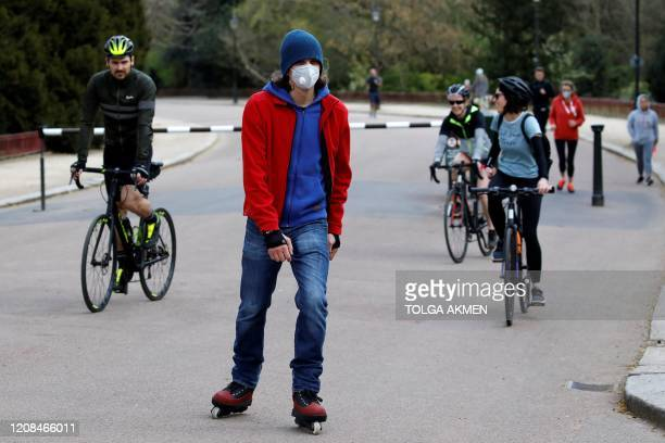People wear face masks as a precautionary measure against Covid19 as they take their daily exercise allowance in Battersea Park in London on March 28...
