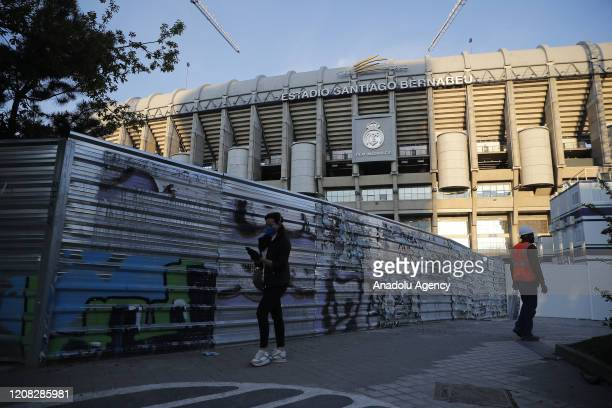 People wear face masks as a preventive measure against the coronavirus pandemic in front of the Santiago Bernabeu Stadium in Madrid Spain on March 26...