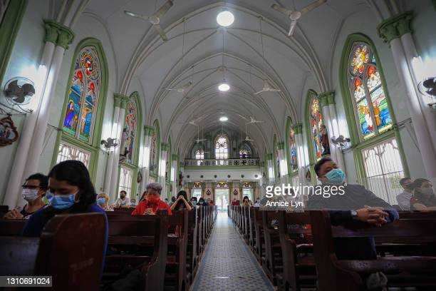 People wear face masks as they attend an Easter Sunday mass service on April 04, 2021 in Kuala Lumpur, Malaysia. As the country eased its COVID-19...