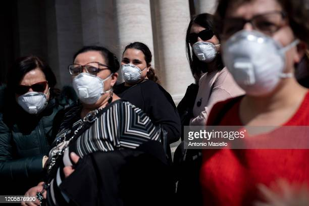 People wear face masks as they attend the live-broadcasting of Pope Francis' Sunday Angelus prayer during the Coronavirus emergency at Saint Peter's...