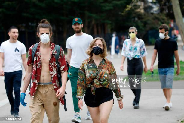People wear face masks as they take their daily excercise in Victoria Park in east London on April 11, 2020 as warm weather tests the nationwide...