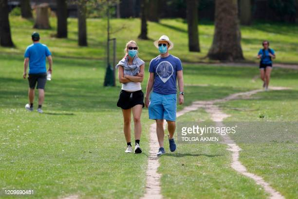 People wear face masks as they take their daily excercise in Victoria Park in east London on April 11 2020 as warm weather tests the nationwide...