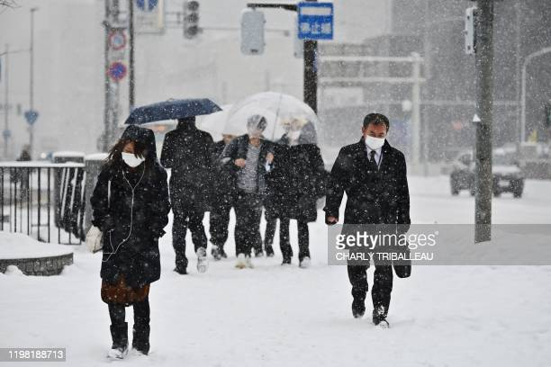 People wear face masks as they walk along a street during snowfall in Sapporo, northern Japan on February 3, 2020. - Japan's health ministry reported...