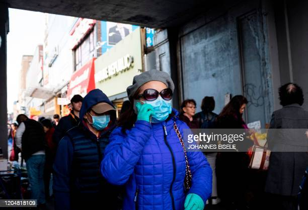 People wear face masks as they walk down a street in Flushing area of Queens on March 2, 2020 in New York City. - New York's governor, Andrew Cuomo,...