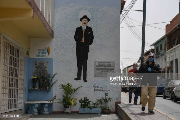 People wear face masks as they walk near a mural with an image of Venezuelan doctor Jose Gregorio Hernandez at the site he was killed 101 years ago...