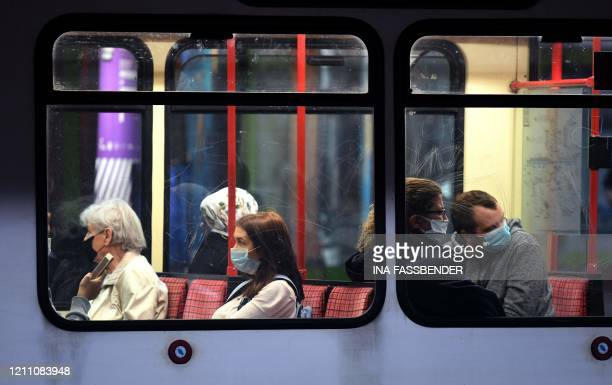 People wear face masks at a UBahn commuter train station in Dortmund on April 27 amid the new coronavirus COVID19 pandemic Protective masks will be...