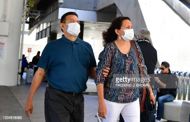 People wear face masks at Los Angeles International Airport in Los Angeles California on March 2 2020 The number of US deaths from the novel...