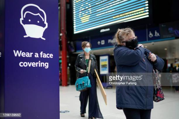 People wear face masks at the train station on July 14 2020 in Liverpool United Kingdom The UK government has announced that people entering shops...