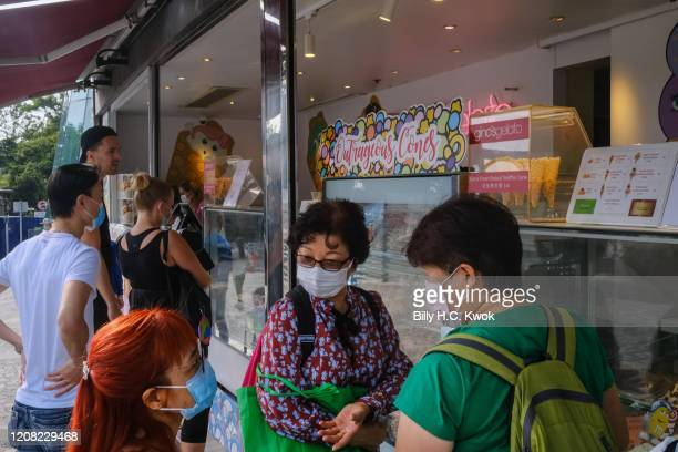 People wear face masks buying ice cream during a coronavirus outbreak on March 26 2020 in Hong Kong China Latest statistics showed Hong Kong tourist...