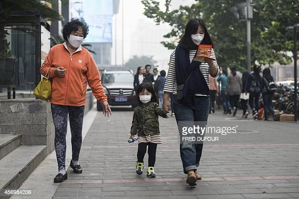 People wear face masks in Beijing amid heavy smog on October 10 2014 Days of heavy smog shrouding swathes of northern China pushed pollution to more...