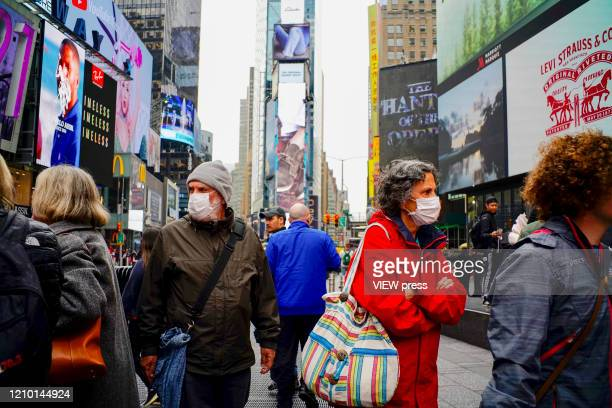 People wear face masks in Times Square New York on March 03 2020 New York confirms second coronavirus case as flights cancelations and Jewish schools...