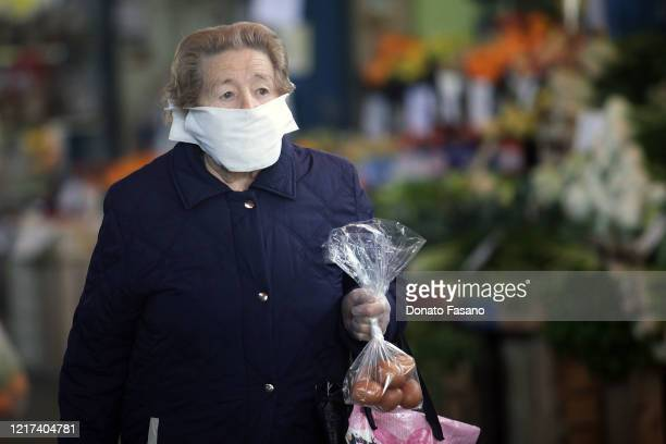 People wear face masks intent on shopping for Easter week in the local market of Carrassi on April 07 2020 in Bari Italy There have been well over...