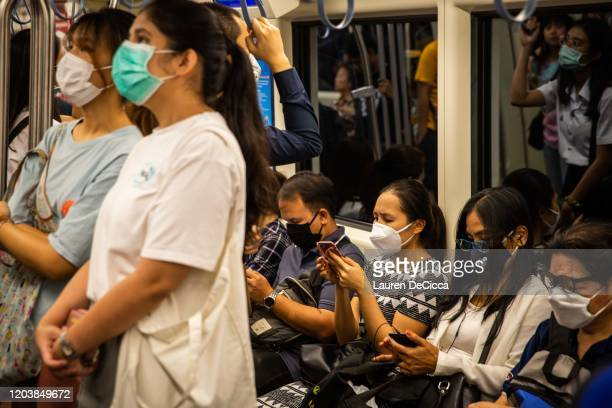 People wear face masks on the MRT train on February 28 2020 in Bangkok Thailand Thai citizens and tourists have taken measures such as wearing masks...