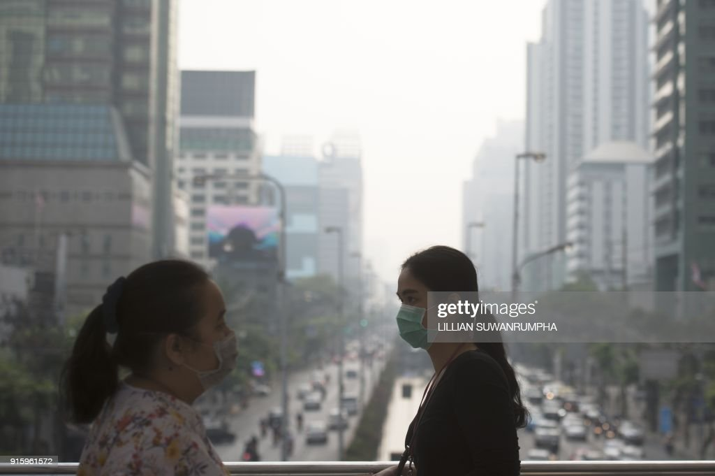People wear face masks on their way to work in the business district of Bangkok on February 9, 2018. The Pollution Control Department advised those with respiratory diseases to take precautions whilst outdoors on February 8, due to the highest PM indexes seen in recent days. /