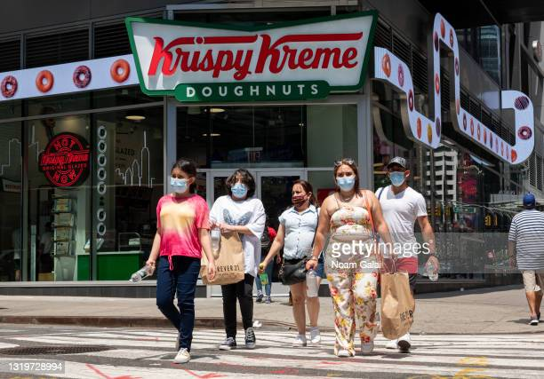 People wear face masks outside Krispy Kreme in Times Square on May 23, 2021 in New York City. On May 19, all pandemic restrictions, including mask...