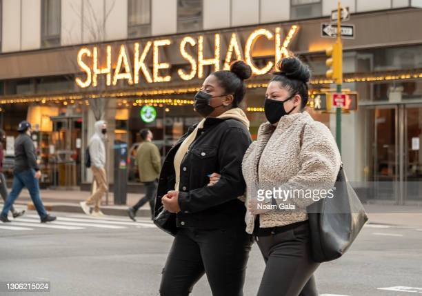 People wear face masks outside Shake Shack in Hell's Kitchen amid the coronavirus pandemic on March 09, 2021 in New York City. It has been one year...