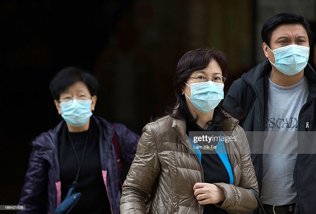 People wear face masks outside the Princess Margaret Hospital on April 12, 2013 in Hong Kong. Local authorities have stepped up the testing of live poultry imports from China to include a rapid test for the H7N9 'bird flu' virus. Measures were put in place as the tenth victim of the influenza strain was confirmed in mainland China yesterday.