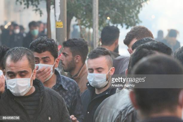 People wear face masks to cover from the tear gas smoke while demonstrators clash with riot police within antigovernment protests in Sulaymaniyah...
