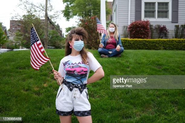 People wear face masks while participating in the annual Memorial Day Parade on May 25 2020 in the Staten Island borough of New York City Dozens of...