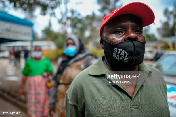 People wear face masks while queueing during a mass testing for COVID-19 coronavirus provided free of charge by the Kenyan government in the Kibera...