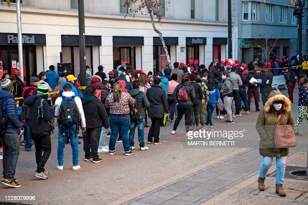 People wear face masks while queueing to enter a branch of the Pension Fund Administrators office to start the procedure to withdraw up to a ten...