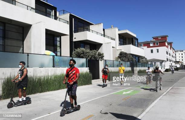 People wear face masks while riding along the Venice Beach boardwalk amid the COVID-19 pandemic on July 2, 2020 in Venice, California. Beginning July...