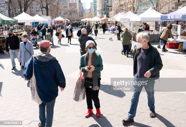People wear face masks while shopping at the Union Square Greenmarket amid the coronavirus pandemic on March 10, 2021 in New York City. It has been...