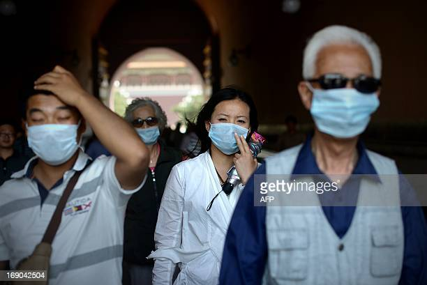 People wear face masks while visiting the Forbidden City in Beijing on May 19 2013 China will more than double the number of cities covered by air...