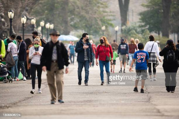 People wear face masks while walking at The Mall in Central Park amid the coronavirus pandemic on March 11, 2021 in New York City. After undergoing...