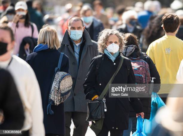 People wear face masks while walking at the Union Square Greenmarket amid the coronavirus pandemic on March 10, 2021 in New York City. It has been...